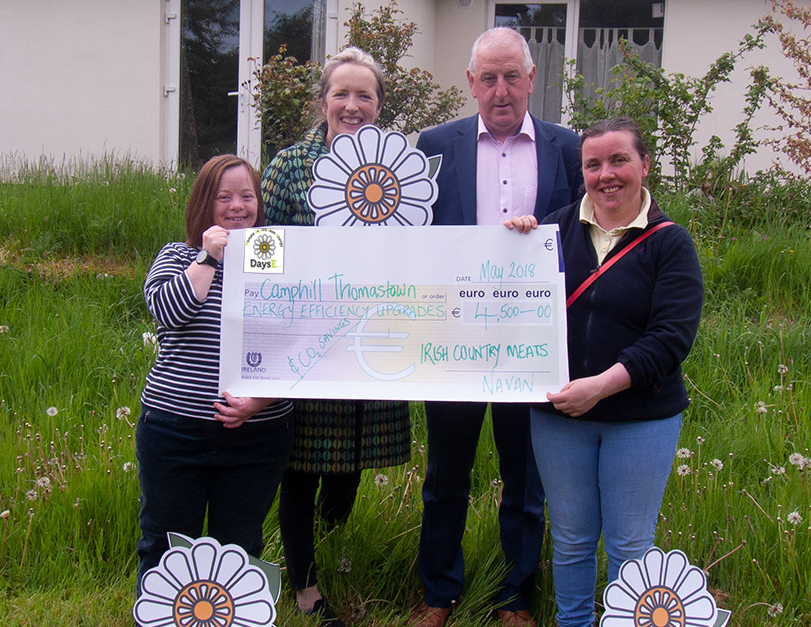 Members of The Watergarden team stand in a sunny garden with Grace Hamilton, DaysE and Liam Walsh, Irish Country Meats at the handover of the donation towards Camphill's energy efficiency upgrade.